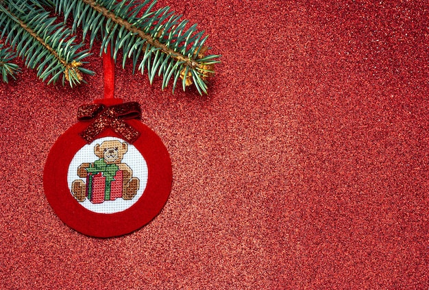 빨간 배경에 십자수 테디베어가 있는 공 형태의 펠트로 만든 수제 빨간 크리스마스 트리 장난감
