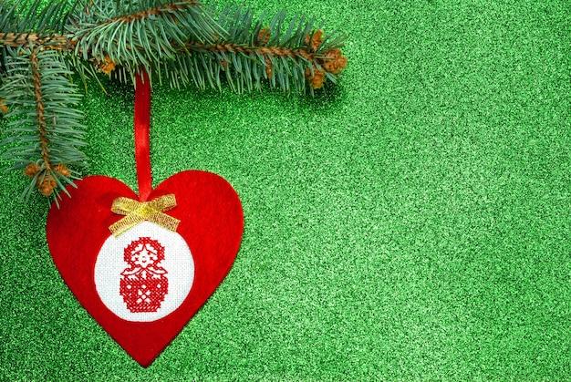 녹색 배경에 십자수 마트료시카가 있는 하트 형태의 펠트로 만든 수제 빨간 크리스마스 트리 장난감