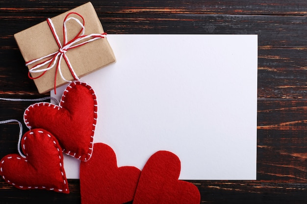 Handmade red felt heart and gift, next to white paper, on wooden table
