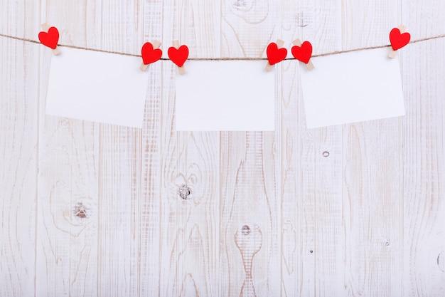 手作りの赤いフェルトハートと洗濯はさみでロープにぶら下がっているホワイトペーパー