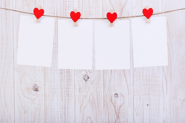 Handmade red felt hearts and white paper hanging on a rope with clothespins