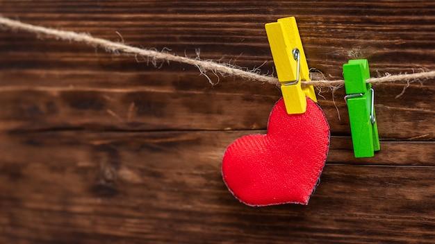 Красное сердце ручной работы, прикрепленное к веревке с помощью прищепки. открытка ко дню святого валентина