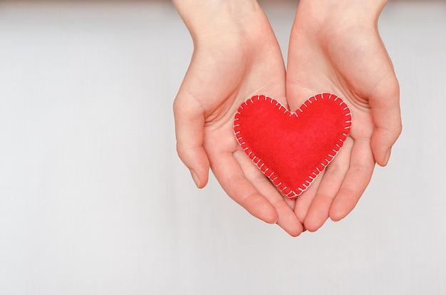 コピースペースのある白いテーブルの上の女の子の手に手作りの赤いハート。バレンタイン