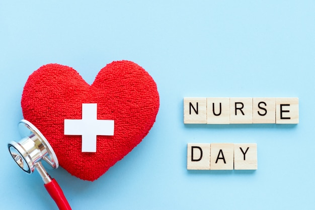 Handmade red heart with stethoscope and nurse day wooden block on blue background.