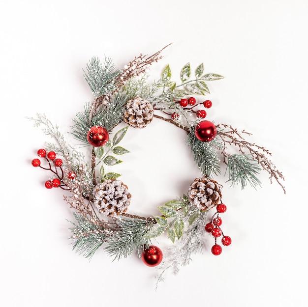 Многоразовый рождественский венок ручной работы из синтетических веток деревьев, красных ягод, шишек на белом Premium Фотографии