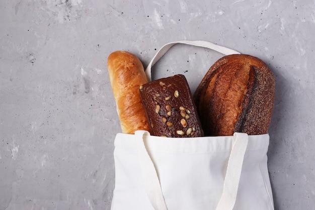 灰色のコンクリートの背景に焼きたてのパンと手作りの再利用可能な綿織物のショッピングバッグ。ゼロウェイスト、環境にやさしいショッピングとエコロジーのコンセプト。上面図、コピースペース