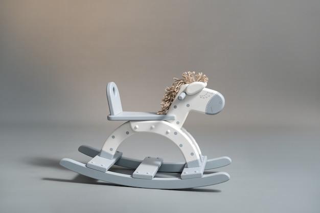 Handmade rocking horse on a gray wall