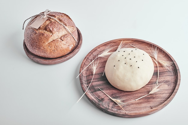 Handmade round bread bun dough with a cooked one in a wooden platter.