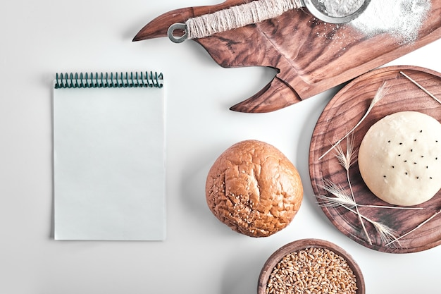 Handmade round bread bun dough in a wooden platter with a recipe book aside.