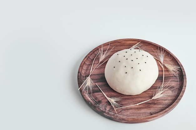 Handmade round bread bun dough in a wooden platter.