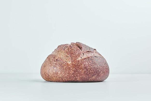 Handmade round bread bun on grey table.