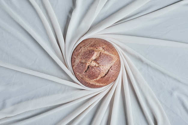 Handmade round bread bun in the middle of a tabletloch.