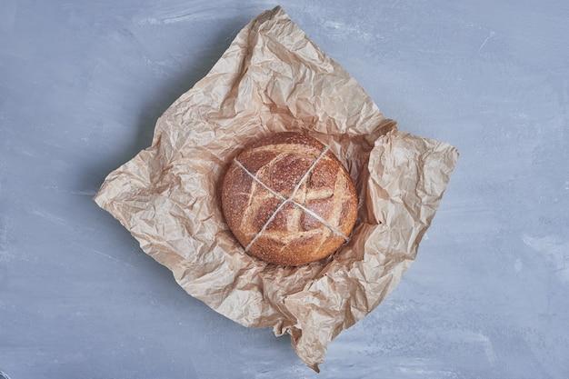 Panino di pane tondo fatto a mano su carta.