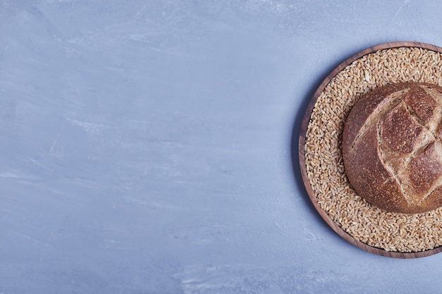 Handmade round bread bun on the wheat platter, top view.