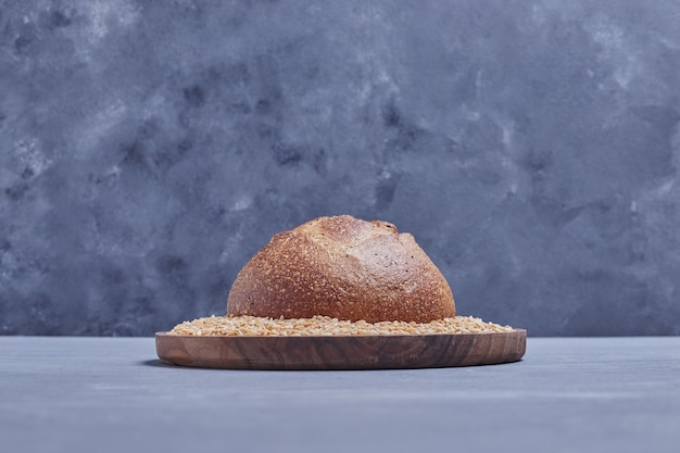Handmade round bread bun on the wheat platter.