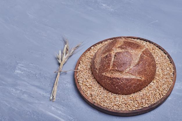 Handmade round bread bun on a wooden platter.