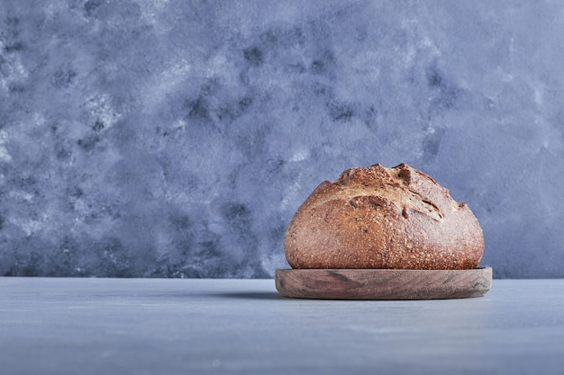 Handmade round bread on grey table on a wooden platter.