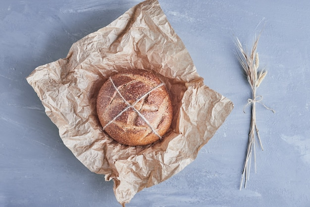 Handmade round bread on a piece of paper.