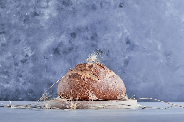 Handmade round bread on a wooden board.