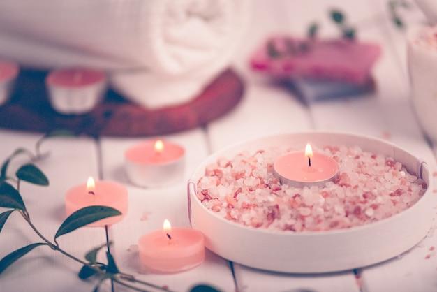 Скраб ручной работы с персиком и солью с аргановым маслом. гималайская соль. туалетные принадлежности, спа-набор со свечами и белым полотенцем. мягкий свет в стиле ретро.