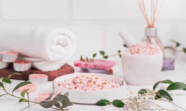 Скраб ручной работы с персиком и солью с аргановым маслом. гималайская соль. туалетные принадлежности, спа-набор со свечами и белым полотенцем.