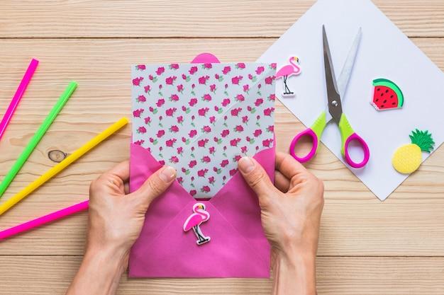 Cartolina d'auguri di scrapbook fatti a mano in busta rosa sulla scrivania