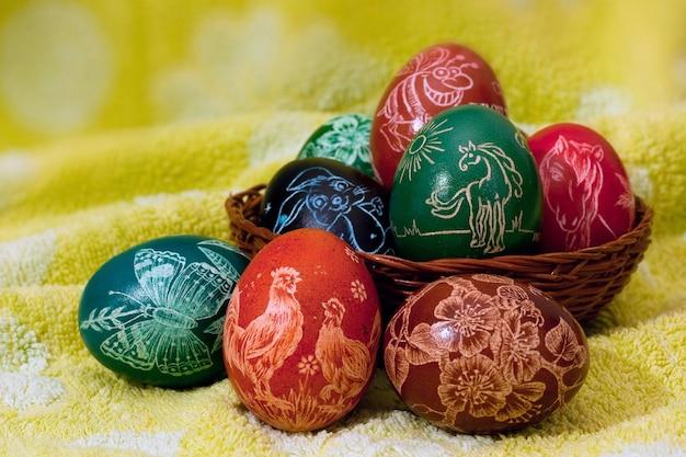밝은 노란색 배경에 농장 동물과 꽃으로 장식된 수제 긁힌 다채로운 부활절 달걀