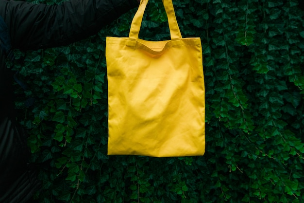 Handmade shopping bag on green plant background. blank canvas bag, design mockup with hand.