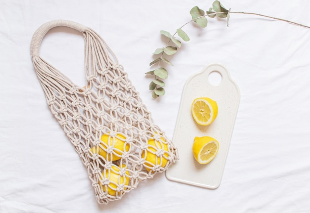 Handmade shopping macrame bag with lemon on white cotton background
