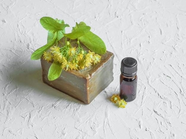 Мыло ручной работы и цветы липы на белом столе.