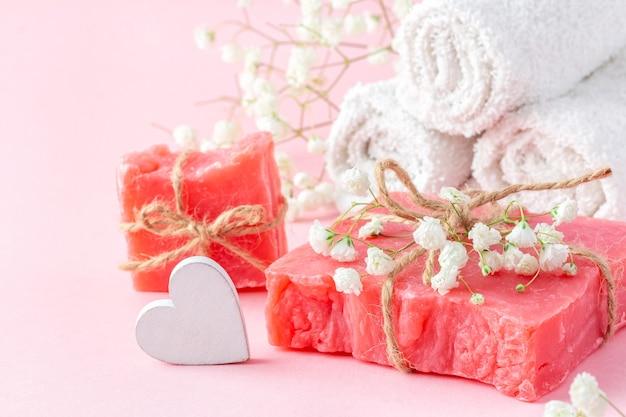 Кусковое мыло ручной работы и белые полотенца, украшенные гипсофилой на розовом