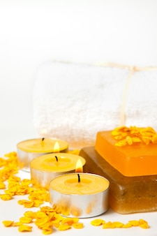 Handmade soap, candles and towels on a white background, vertical frame