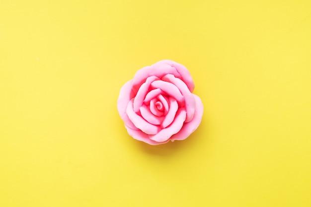 黄色の背景にバラ、ピンクのバラの花の形をした手作り石鹸。上面図、ミニマリスト、コピースペース。