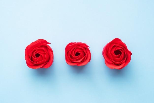 青い背景にバラ、赤いバラの花の形をした手作り石鹸。上面図、ミニマリスト、コピースペース。