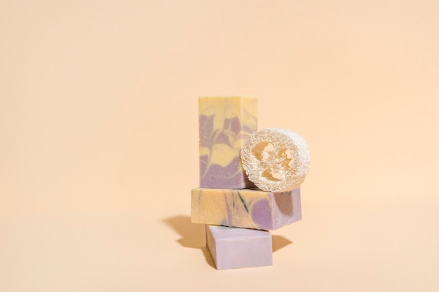 Handmade soap and loofah sponge on a cream color background