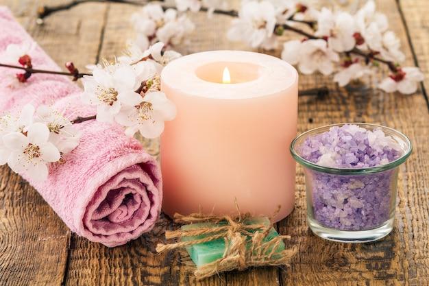 손수 만든 비누, 유리 그릇에 바다 소금을 말아 수건으로 덮고 배경에 살구나무의 꽃가지와 함께 불타는 촛불. 스파 제품 및 액세서리