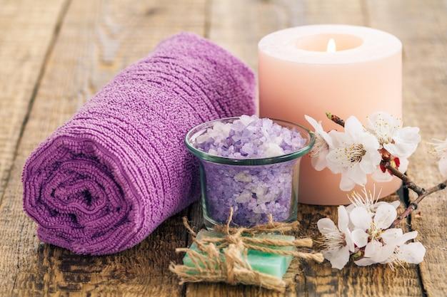 손수 만든 비누, 유리 그릇에 바다 소금을 말아 수건과 살구 나무의 꽃 가지와 함께 불타는 촛불. 스파 제품 및 액세서리