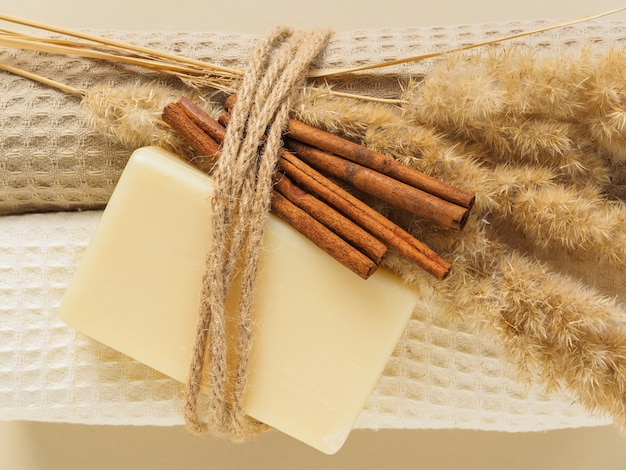 Handmade soap, towels, dried plants and cinnamon tied with rope on beige