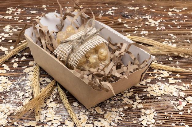 Мыло ручной работы с овсяными хлопьями на деревянном фоне с ушами. натуральная органическая домашняя косметика для ухода за кожей. скраб для кожи.