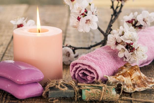 말린 수건, 바다 조개, 살구 나무의 꽃 가지가 있는 불타는 촛불이 있는 수제 비누. 스파 제품 및 액세서리