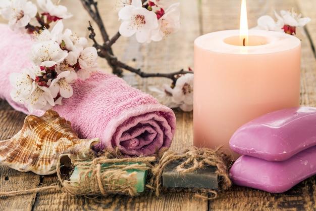 욕실 절차를 위한 수건이 있는 수제 비누, 바다 조개, 살구 나무의 꽃가지와 함께 타는 촛불. 스파 제품 및 액세서리