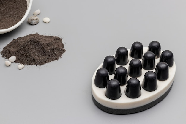 Мыло ручной работы с белой и темной глиной на сером фоне. натуральная органическая домашняя косметика для ухода за кожей. скраб для кожи. антицеллюлитные процедуры.