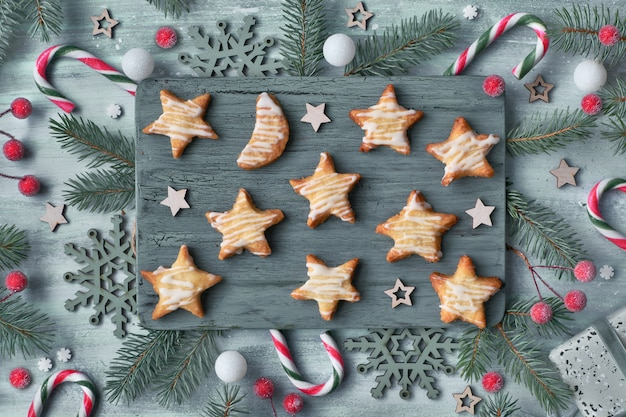 Handmade star-shaped christmas cookies on cutting board, flat lay with xmas decorations