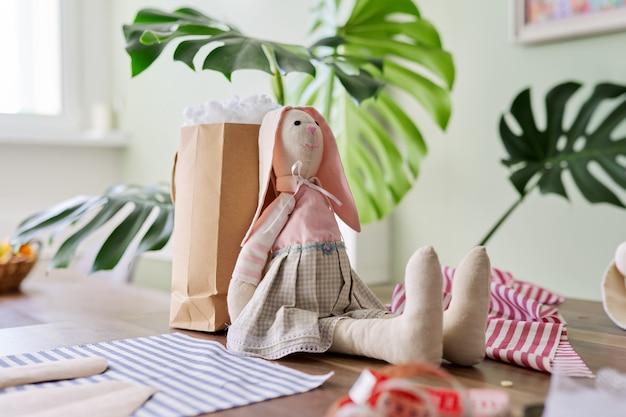 Текстильная игрушка ручной работы зайчик девочка сидит на столе, пошив авторских кукол дома, пасхальный заяц, хобби и досуг, концепция мастерства