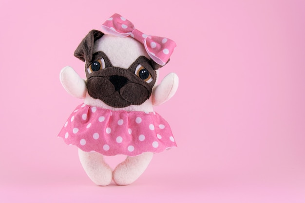 Handmade toy dog of pug breed on a pink background