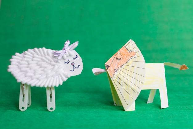 緑の背景に白い羊とライオンの手作りおもちゃ