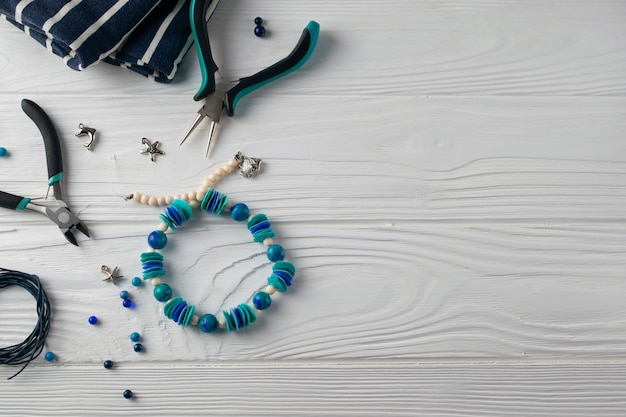 Handmade turquoise bracelet, craft set with pliers, cord and beads, flat lay