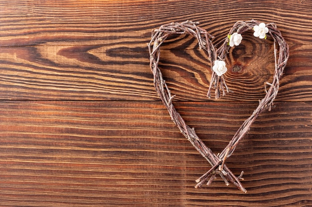 Handmade twigs heart on wood background for valentine day or mothers day