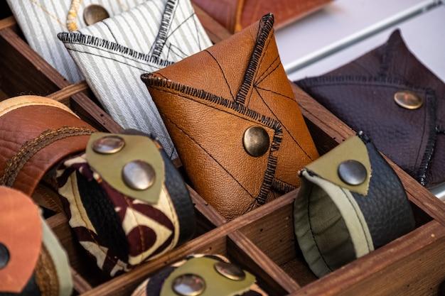 革と布で作られた手作りの財布とブレスレット、金属製のリベットが店の棚にあります。ファッションアクセサリー。