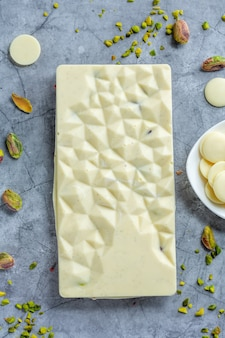 Handmade white chocolate bar with pistacchios and dry raspberries on bright background. top view.